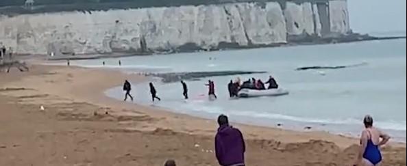 Šokujúce video. Migranti oslavujú pristátie na pláži Broadstairs v Kente pred prekvapenými opaľujúcimi ľuďmi. V člne ich bolo 20 vrátane 3 detí
